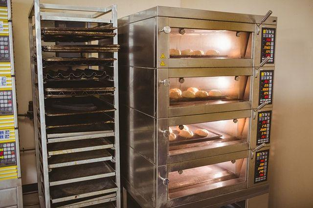 un porta vassoi in metallo e dei forni in metallo con del pane infornato