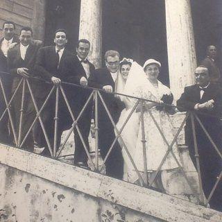 un'immagine in bianco e nero di due sposi e delle persone accanto sulle scale