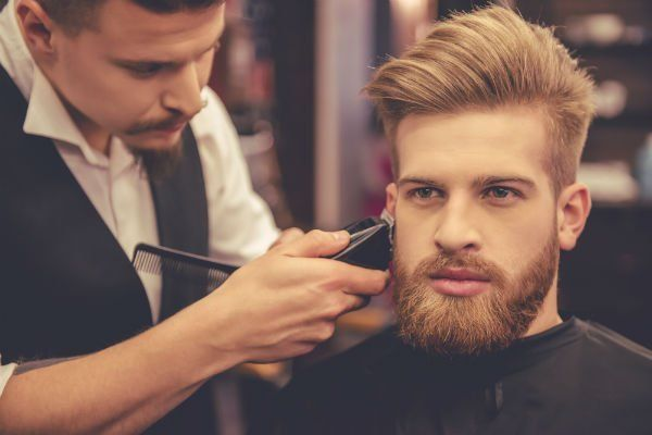 un parrucchiere con una macchinetta e un ragazzo seduto con barba e capelli.biondi