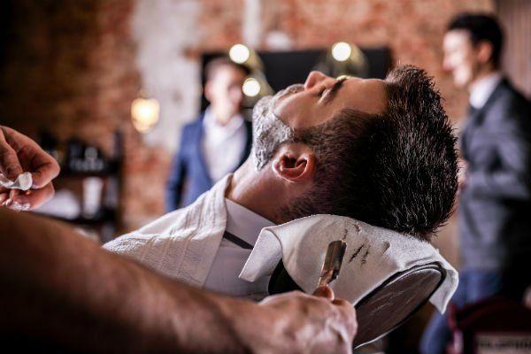 un ragazzo con capelli neri e barba sdraiato sulla poltrona da un parrucchiere