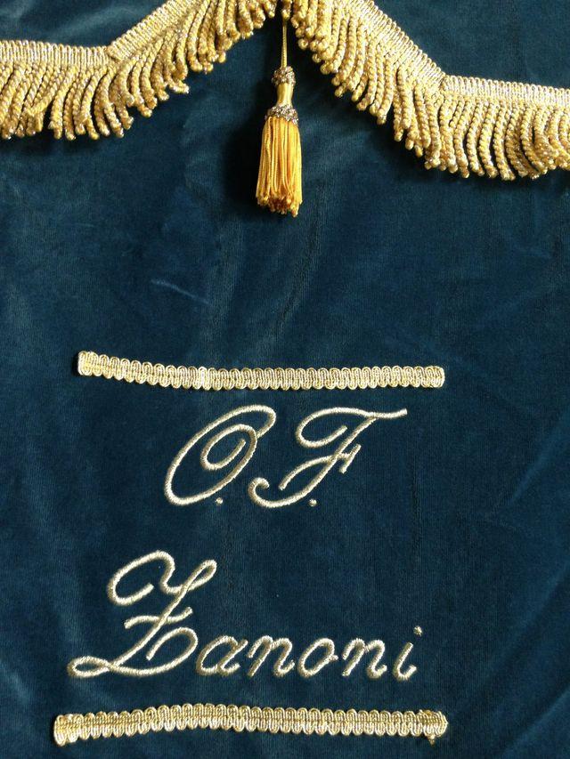 tessuto in velluto blu ricamato con le iniziali dell'agenzia funebre