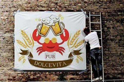 uomo monta cartellone con insegna pubblicitaria del pub dolce vita
