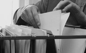 A man sorting through a file of documents