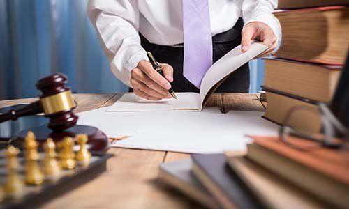 Dopo vari libri, parte di una scacchiera e un martello di giustizia, si vede una mano scrivendo un documento