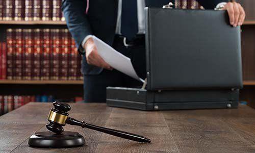 Biblioteca legale al fondo una mano osserva documenti in un maletin di fronte a un martello di giustizia