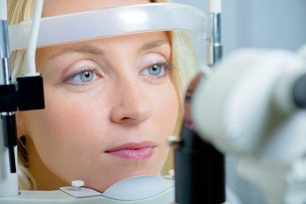 Donna con il mento sostenuto dalla macchina che esamina i suoi occhi