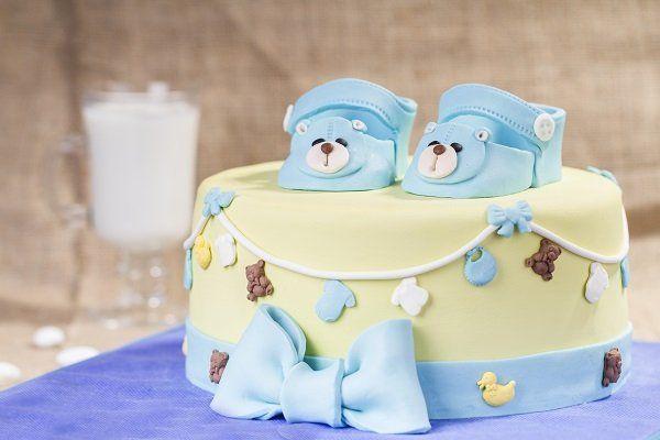 una torta con glassa gialla e azzurra,un fiocco e due scarpine con degli orsetti
