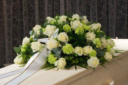 Una composizione di rose bianche su una bara
