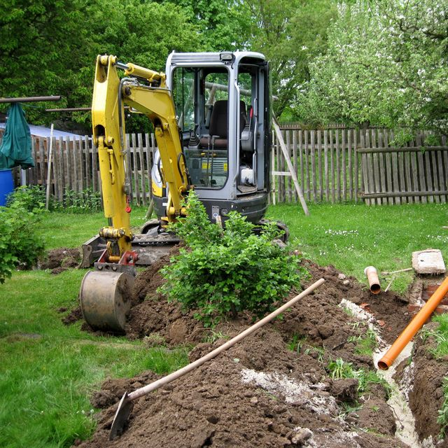 A mini digger being used for performing maintenance to a septic tank