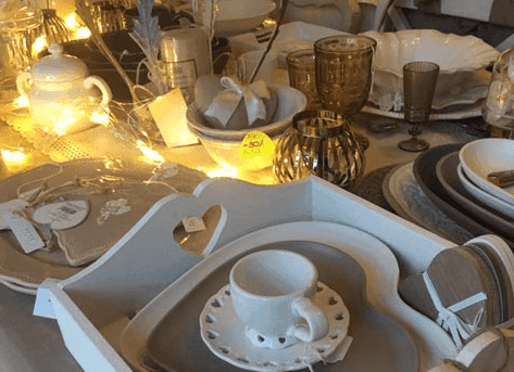 un vaso di color grigio con dei fiori bianchi e delle luci a forma di stella