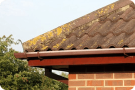 Brown guttering on the corner of a slate roof