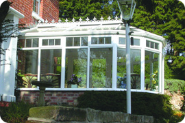 Conservatory with white frame. Half glass and half brick