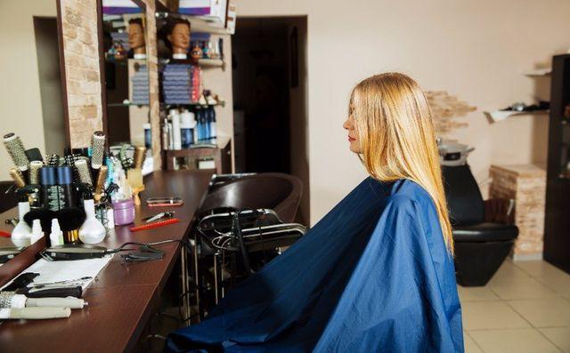 una donna con i capelli biondi lisci seduta da un parrucchiere