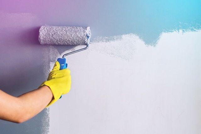 mano con un rullo dipingendo una parete de viola