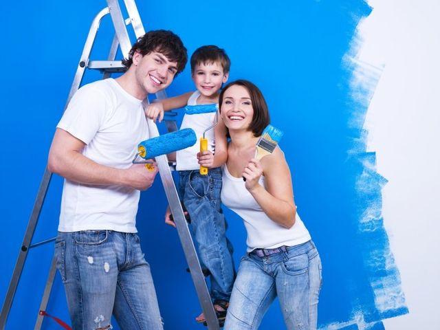 Famiglia dipingendo una parete di blu. La madre ha una spazzola e il bambino e il padre un rullo ciascuno