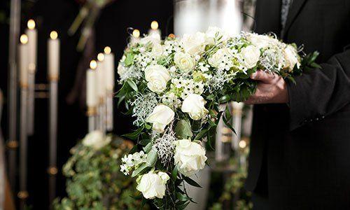 un uomo con in mano un bouquet di fiori bianchi
