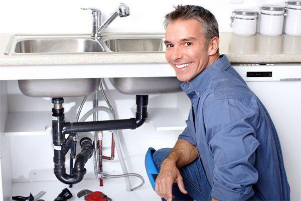 idraulico sorridente accanto a un lavello