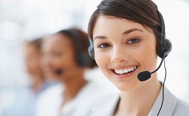 ragazza sorridente con cuffie con microfono integrato lavora in assistenza clienti