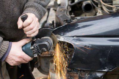 meccanico che lima la carrozzeria di una macchina