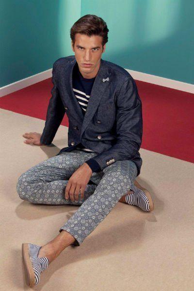 un uomo con dei pantaloni blu, una giacca di jeans e delle espadrillas a righe