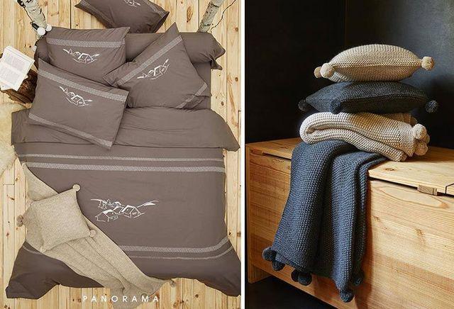 Un completo da letto esposto su uno sfondo di legno chiaro e sulla destra dei copricuscini e copertine in lana esposte su una scatola in legno