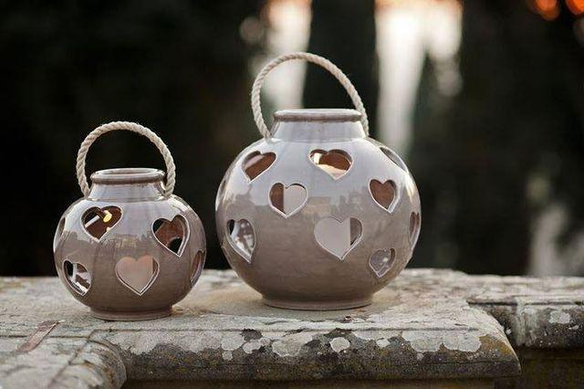 Due lanterne in ceramica di color marrone chiaro con dentro delle candele bianche che si vedono tra i disegni a cuoricini