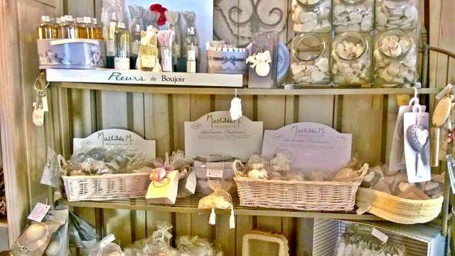 Scaffali con dei cestini di paglia con dei sacchettini,  boccette con fiocchi  e una scritta Fleurs de Boujoir