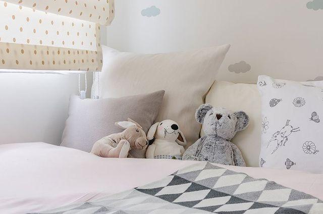 Vista ravvicinata dei cuscini bianchi di varie dimensioni e  peluche su un lettino