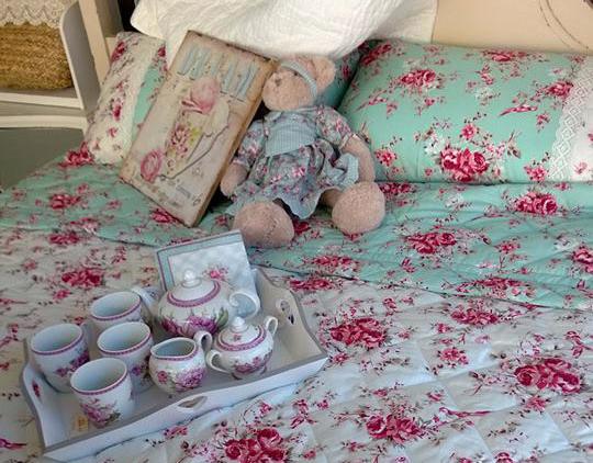 Un letto matrimoniale con copriletto, federe di color turchese con dei disegni di fiori fucsia e un vassoio con servizio da tè in porcellana appoggiato sul letto