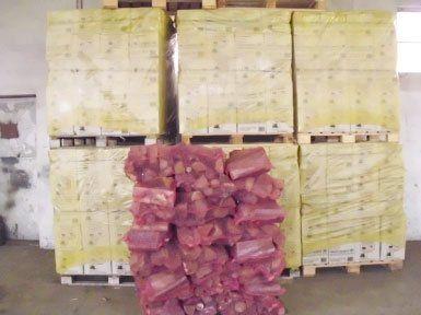 un mucchietto di legna dentro ad una rete rossa e dietro dei bancali con delle scatole coperte da una plastica gialla