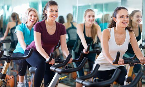 Donne sulle cyclette in palestra