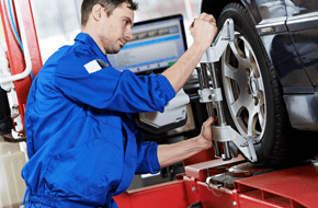 Mechanic checking wheel alignment on a car