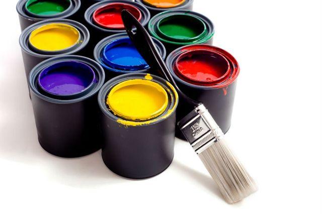 dei barattoli di vernice in vari colori e un pennello