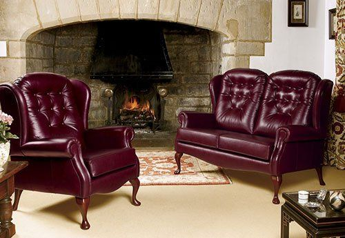 leather sofa and armchair by fireplace