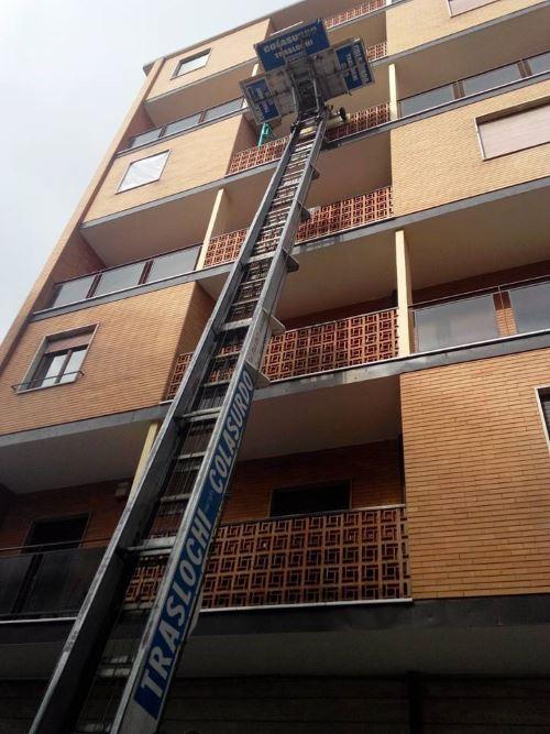 una scala aerea con scritto Traslochi Colasurdo vicino ad un condominio
