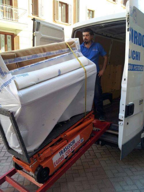 un carrello con un pianoforte imballato e un uomo in piedi all'interno di un furgone