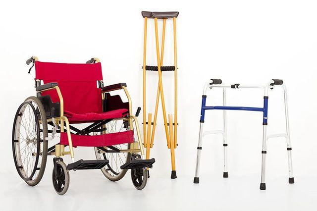 una sedia a rotelle rossa e dei deambulatori