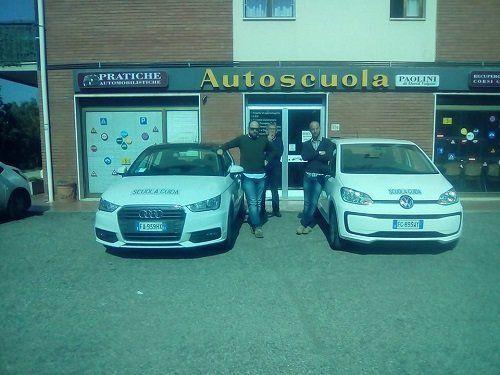 due uomini davanti a un autoscuola vicino a due auto
