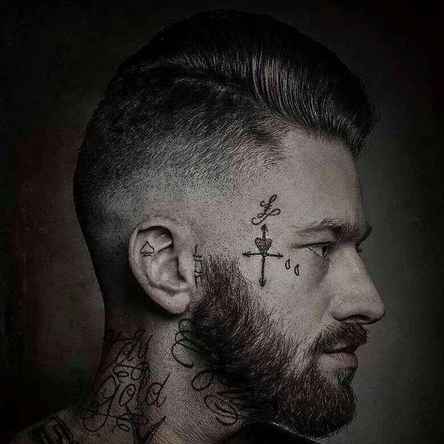 Un uomo con barba, capelli rasati sui lati e in mezzo corti, tatuaggi sul collo e guance