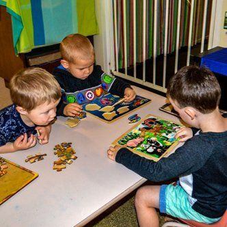 kids doing puzzle on table