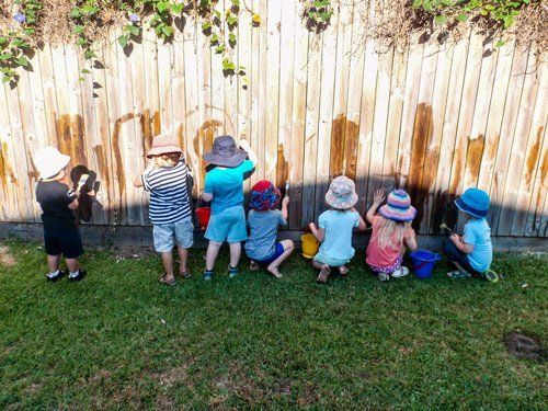 kids playing with water on fence