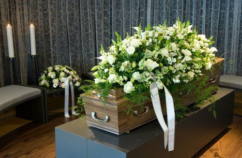 una bara in legno e sopra una corona di fiori