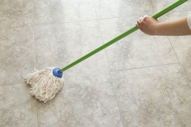 una mano che tiene un mocio durante le pulizie