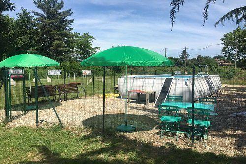 un recinto con due ombrelloni verdi e un tavolo con delle sedie