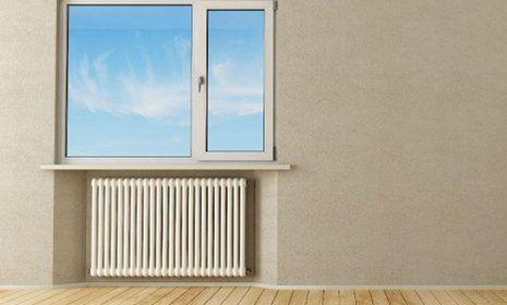 un termosifone e sopra una finestra con rifiniture in pvc color bianco e vista del cielo azzurro attraverso