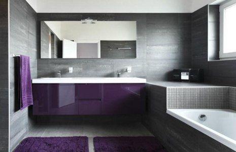 un bagno moderno con un armadio viola con sopra un lavabo e uno specchio, sulla destra una vasca e un tappeto viola al centro
