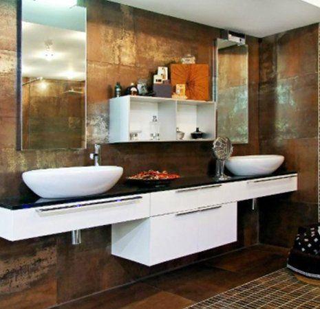 un bagno con pareti di color marrone un mobile bianco con top nero e due lavabi rotondi, sopra uno specchio e un armadietto bianco