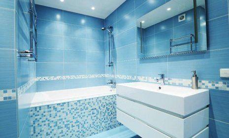 un bagno con piastrelle bianche e azzurre con una vasca da bagno e sulla destra un lavabo con sopra uno specchio