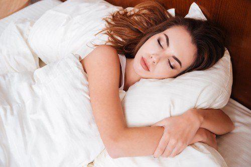 Giovane donna  dorme abbracciata  al suo cuscino