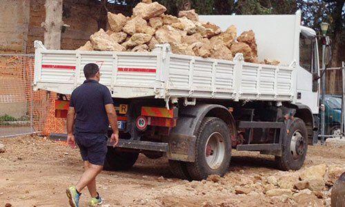Camion carico di pietre e un uomo che cammina